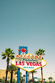 Vintage Americana Las Vegas sign on The Strip, with palm trees and clear blue sky on a sunny day.Vertical composition with copy space.