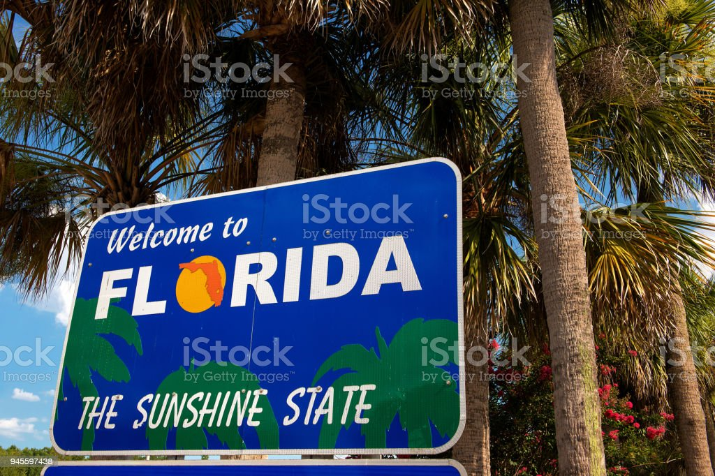 Welcome To Florida Sign With Palm Trees In Background Stock Photo