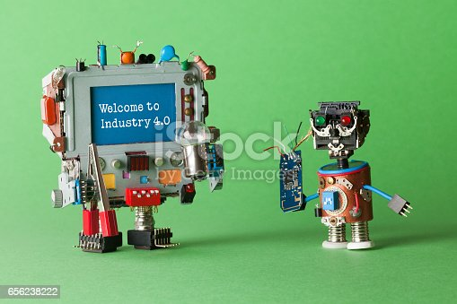 istock Welcome to Industry 4 0 robotic cyber systems, smart technology and automation process. Abstract electronic toy with circuit in hand and monitor computer robotic character, warning message on blue screen. green background macro view 656238222