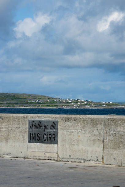 Welcome to Inisheer The welcome sign on ferry dock at Caherard, Inisheer, Aran Islands, County Galway, Republic of Ireland.  Signage within the Gaeltacht (Irish speaking region) is in the Irish language.  This is a view from the dock looking west across the Inisheer coast, homes set in the burren landscape of the island. Inisheer, Aran Islands, County Galway, Republic of Ireland michael stephen wills aran stock pictures, royalty-free photos & images