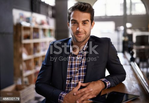 Portrait of a handsome young man standing next to a bar counter