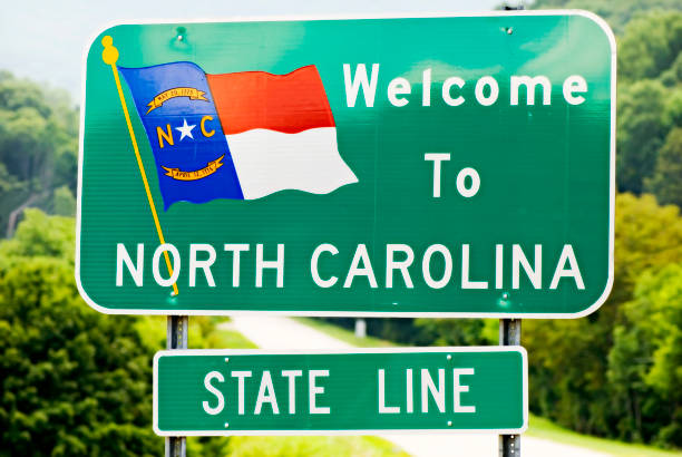 Welcome To North Carolina North Carolina state sign at the border with a road and foliage in the background north carolina us state stock pictures, royalty-free photos & images