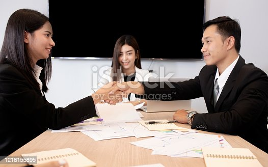 951514270 istock photo Welcome to our team! Top view of young modern men in smart casual wear shaking hands while working in the creative office 1218155895