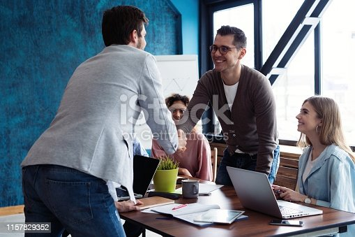 istock Welcome to our team! Young modern men in smart casual wear shaking hands while working in the creative office. 1157829352
