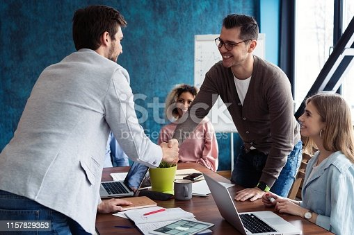 951514270 istock photo Welcome to our team! Young modern men in smart casual wear shaking hands while working in the creative office. 1157829353