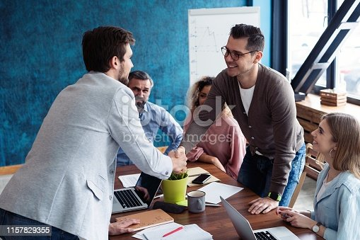 951514270 istock photo Welcome to our team! Young modern men in smart casual wear shaking hands while working in the creative office. 1157829355