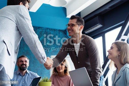 951514270 istock photo Welcome to our team! Young modern men in smart casual wear shaking hands while working in the creative office. 1157829357