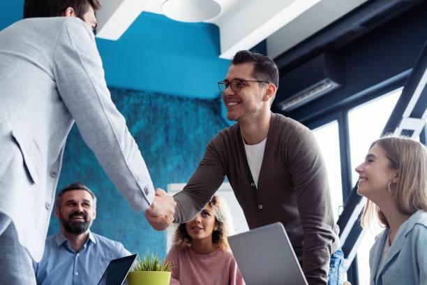 Willkommen in unserem Team! Junge moderne Männer in smartcasual tragen händeschüttelnd, während sie im Kreativbüro arbeiten. – Foto