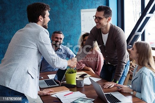 951514270 istock photo Welcome to our team! Young modern men in smart casual wear shaking hands while working in the creative office. 1157829358
