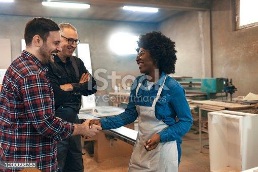 Handshake between female and male carpenters as congratulations. Handshake between carpenter and customer in workshop