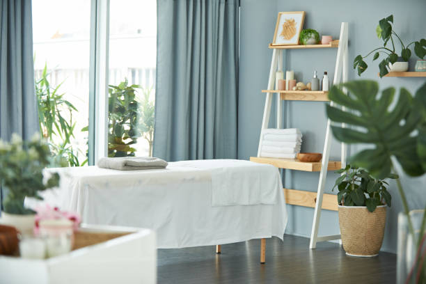 Welcome to paradise Shot of a tranquil massage room with plant life and a massage bed during the day spa stock pictures, royalty-free photos & images