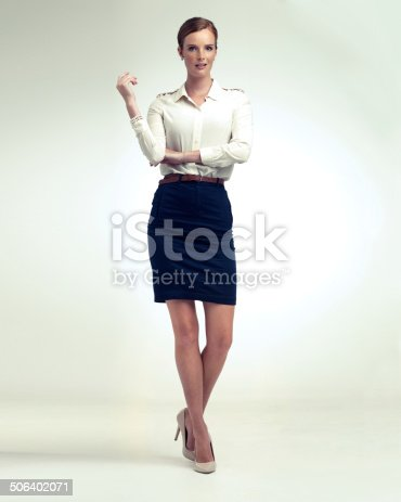 A full length studio portrait of a beautiful young woman in vintage clothing