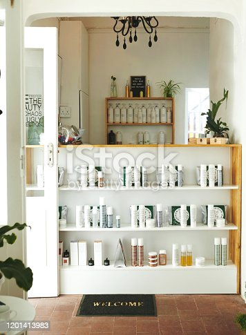 Cropped shot of an empty hair salon reception desk with bottled products stored on shelves