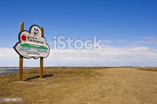 Welcome to Tuktoyaktuk sign with the Arctic ocean and pingo in the background.