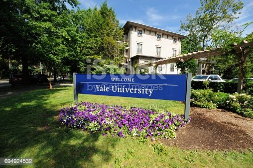New Haven, Connecticut, USA - July 25, 2016: Welcome to Yale University sign located along Trumbull Street in New Haven, Connecticut. Photograph taken with purple flowers blooming under sign.
