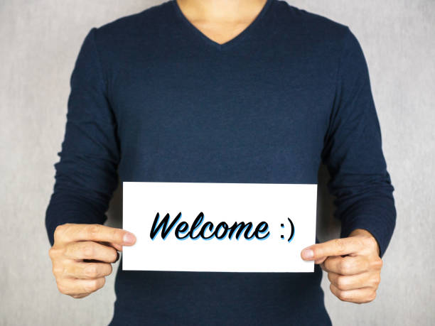 Welcome with smiley face icon sign holding by man, happy and greeting concept stock photo
