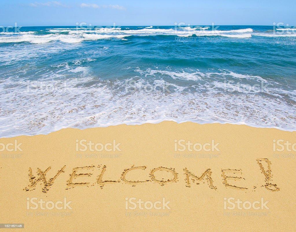 welcome written in a sandy beach stock photo