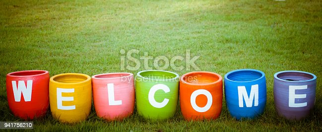 Welcoming and greetings concept with welcome word colorful on garden background.