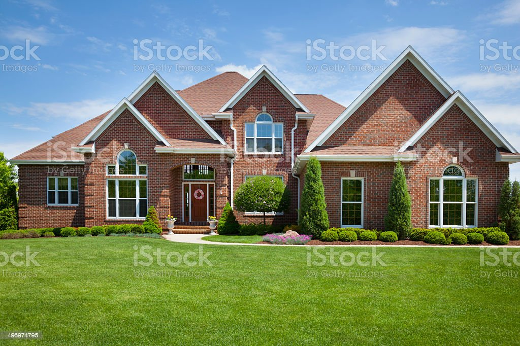 Welcoming Brick Home With Perfect Lawn Welcoming Brick Home With Perfect Lawn.  Brick Stock Photo