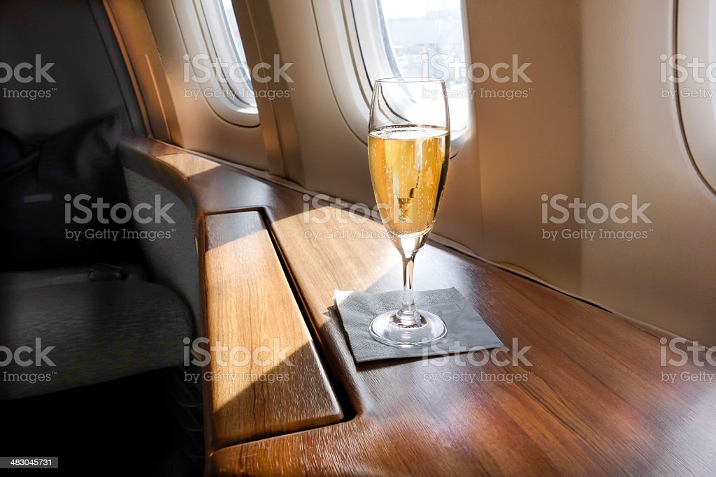 Welcoming Champagne A Glass of Welcoming Champagne awaits a First Class passenger on an Airline Flight Achievement Stock Photo