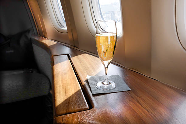 Welcoming Champagne A Glass of Welcoming Champagne awaits a First Class passenger on an Airline Flight first class stock pictures, royalty-free photos & images