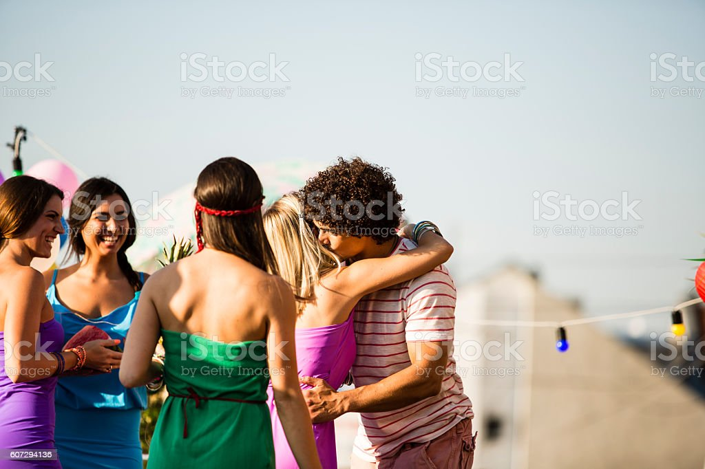 Welcoming friends at rooftop party - foto de stock