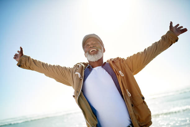 welcoming the sunny side of retirement - arms outstretched stock photos and pictures