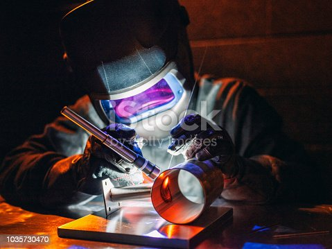 A man using a TIG (Tungsten Inert Gas) welder in a workshop.