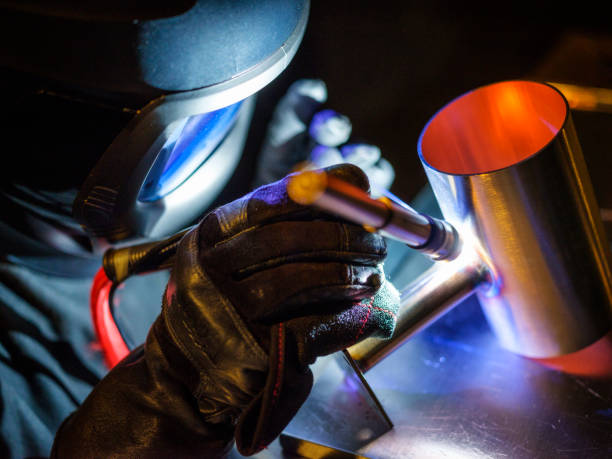 TIG Welder at Work A man using a TIG (Tungsten Inert Gas) welder in a workshop. metalwork stock pictures, royalty-free photos & images