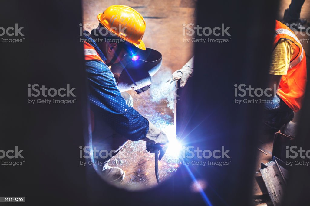 Seen from a persepctive, two welders getting their task done as soon...
