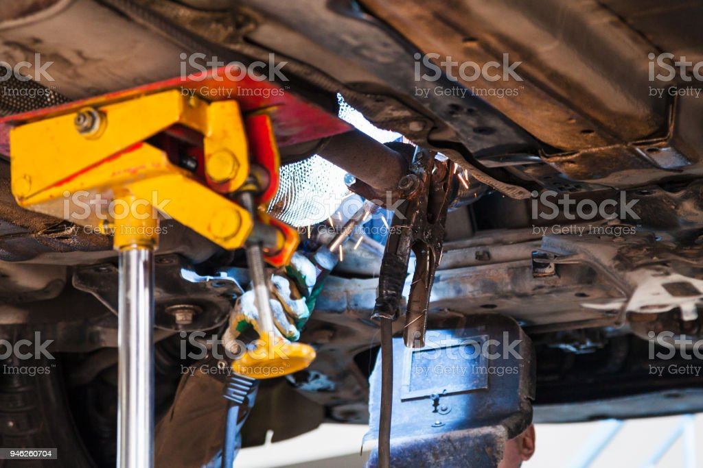 welder fixes silencer on exhaust pipe stock photo