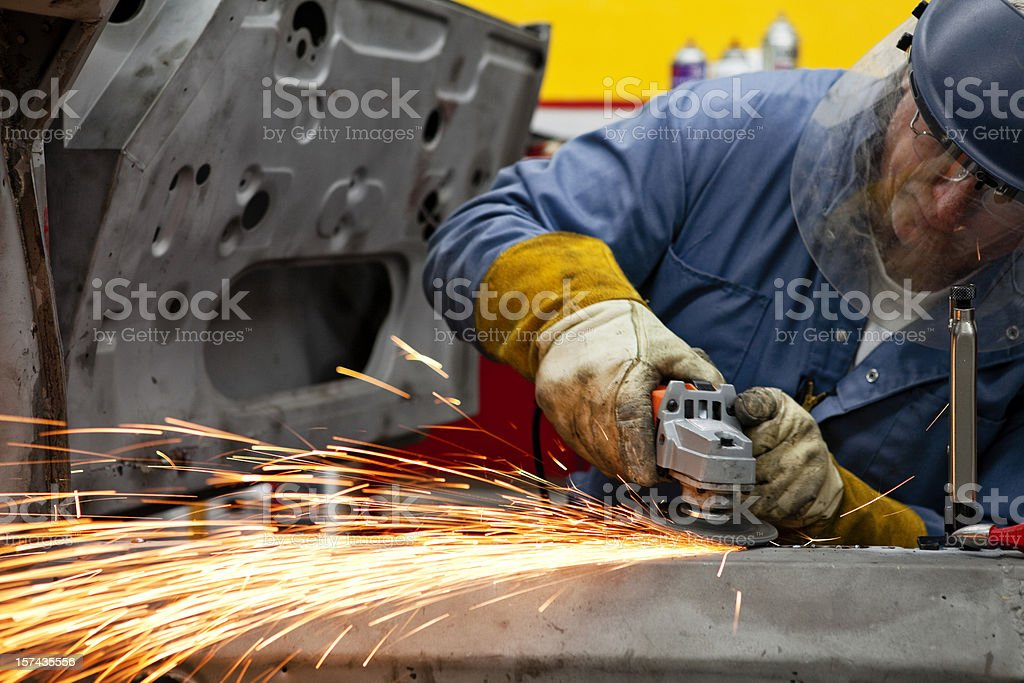 Welder Grinds a Support Piece after Welding in Place royalty-free stock photo