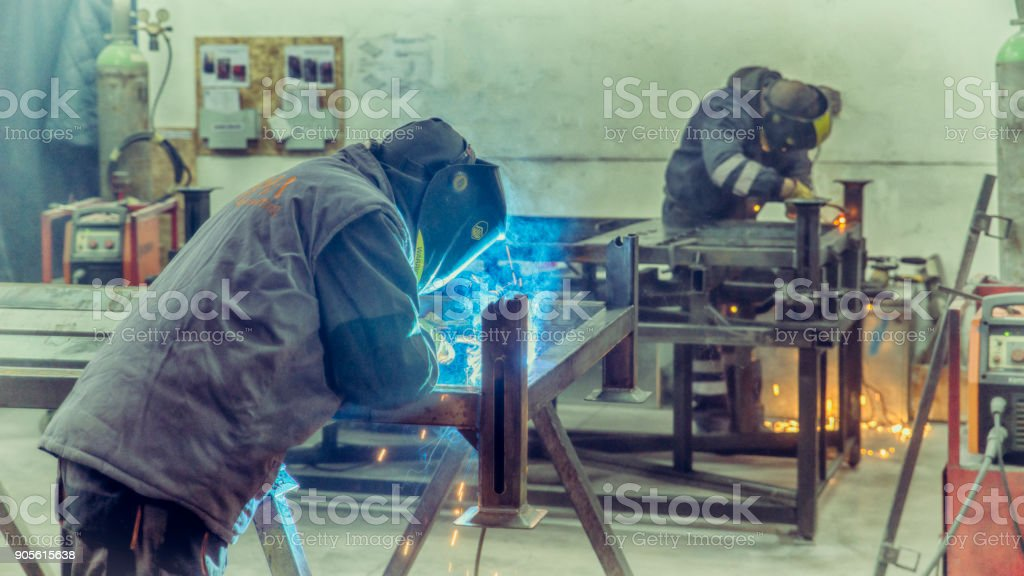 Professional welder in a factory. Semi-automatic welding with sparks...