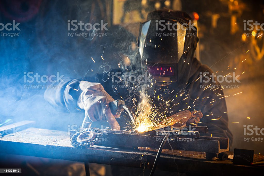 Welder in action with bright sparks. Construction and manufacturing...