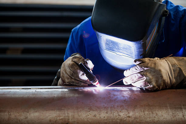 Welder in blue suit with proper protection stock photo