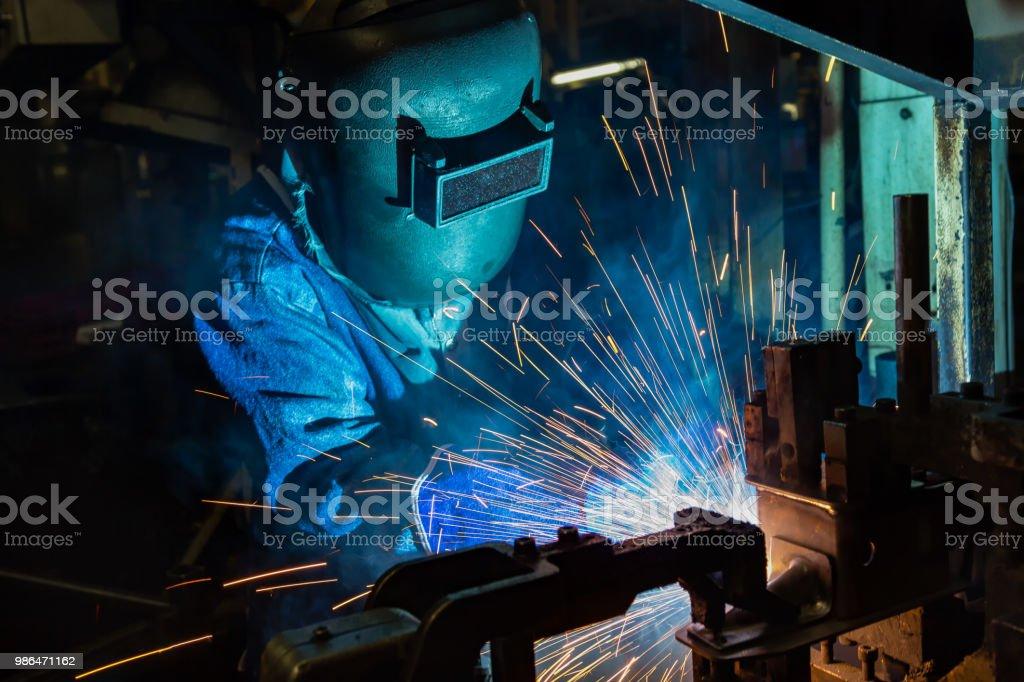 Welder is welding automotive part in production line