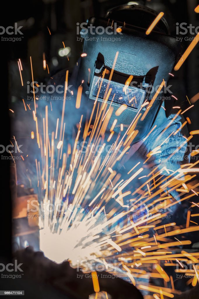 Welder is welding automotive part in production line with protective...