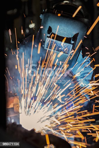 Welder is welding automotive part in production line with protective work wear