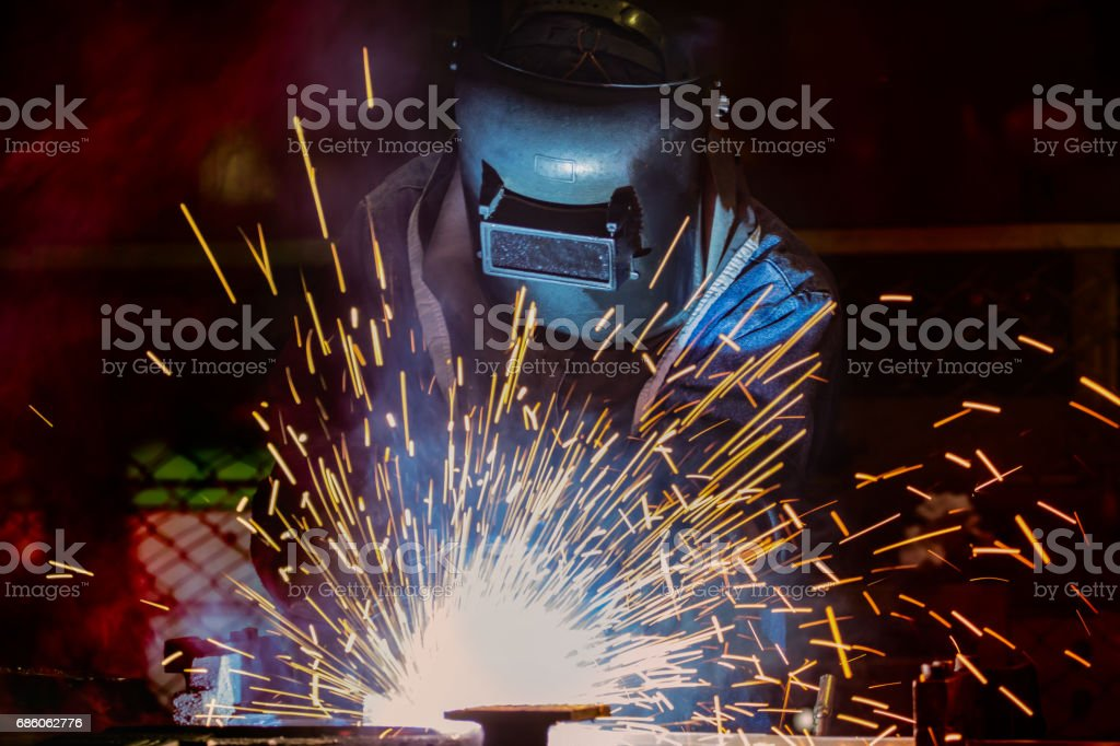 Welder is welding automotive part stock photo