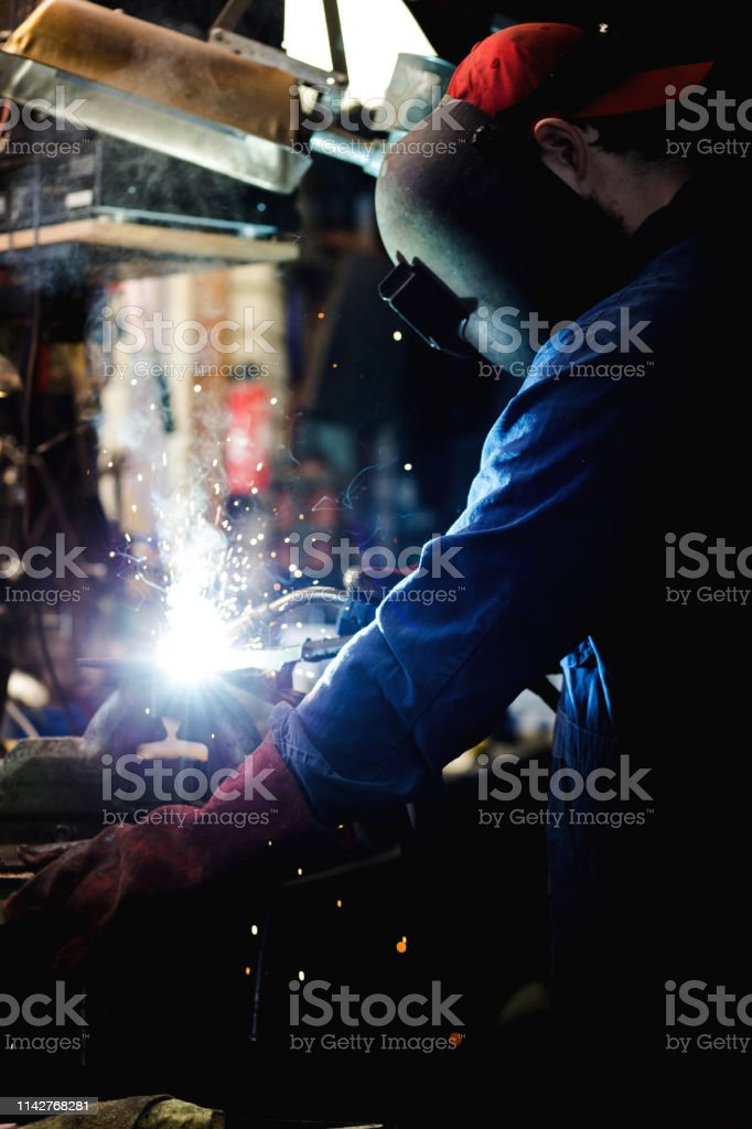 welder is welding metal part in garage. with protective mask,...