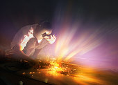 Welder making sparkle explosion while working with light gradient color. Industrial concept