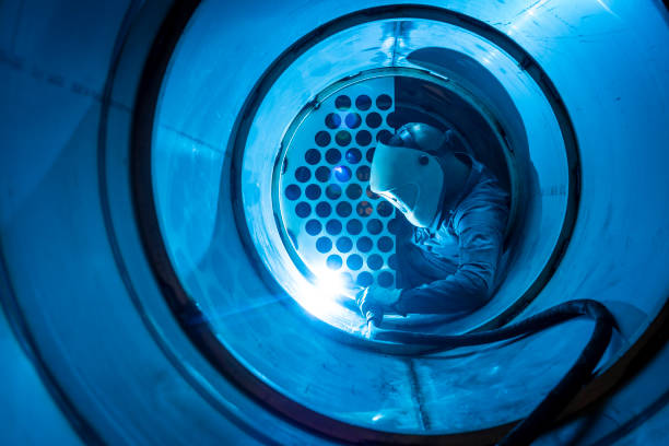 Welder man welding a multitubular heat exchanger Welder man welding a multitubular heat exchanger in boilermaking industry confined space stock pictures, royalty-free photos & images