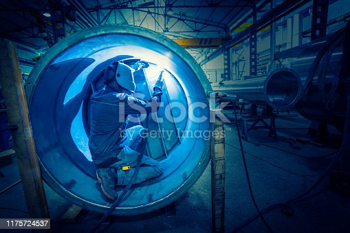 Welder man welding stainless steel tank in boilermaking industry