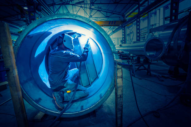 Welder man welding stainless steel tank Welder man welding stainless steel tank in boilermaking industry confined space stock pictures, royalty-free photos & images