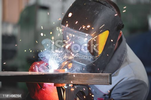 Welder is welding a metal frame.