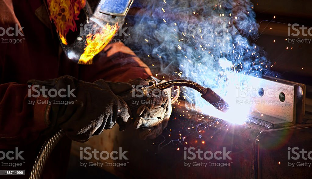 Welder using a torch to fabricate metal hollow structural steel