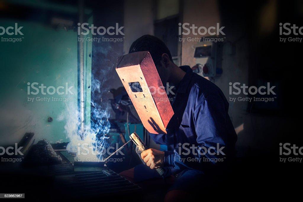 Welder at work, using arc welding with blue light.