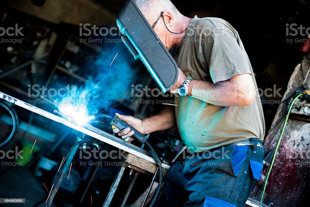 Photo of a man welding the steel or iron. Smoke and sparks around .
