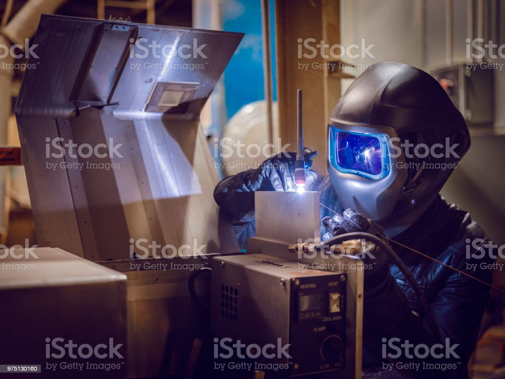 A tig welder works in a production facility to repair a piece of...