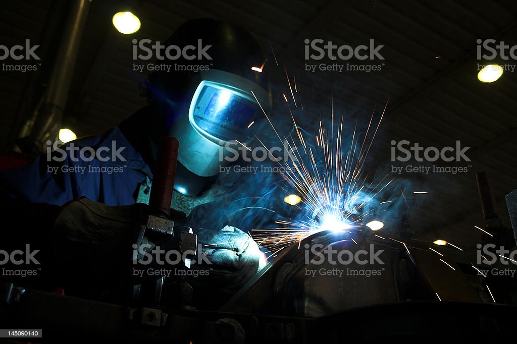 Welder welding a metal part in an industrial environment royalty-free stock photo